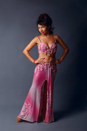 Belly dancer performing belly dance in the ethnic pink costume for dancing on gray background Foto de archivo