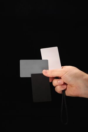 Grey Card. Set of white, black and 18% gray color cards for digital white balance adjustment in a male arm on black background. Photographer's stuff. Archivio Fotografico