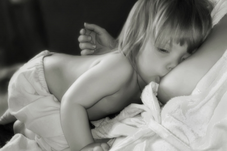 child girl nude: Portrait of the little girl sucking a parent breast Stock Photo