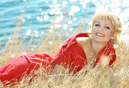 Beautiful blonde in a red dress on a sea resort photo