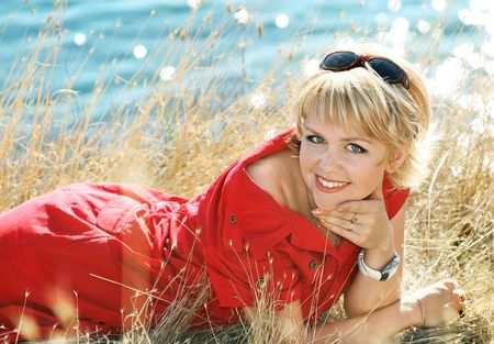 face off: Beautiful blonde in a red dress on a sea resort