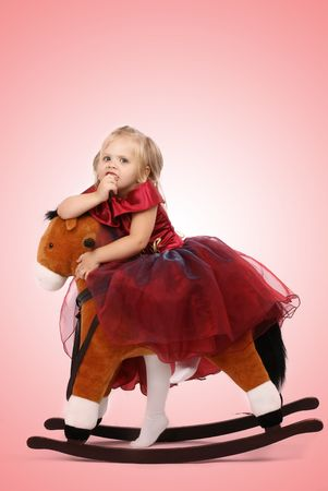 Portrait of the beautiful girl on a toy horse Stock Photo - 3566386
