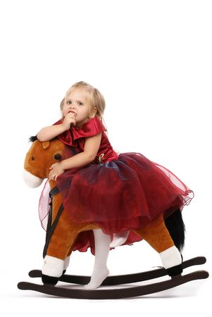 Portrait of the beautiful girl on a toy horse,  photo