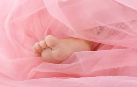 coverlet: Part of a leg of the newborn girl under a pink coverlet