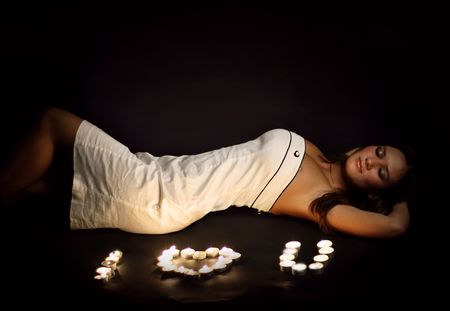 young girl and candles on a black background photo
