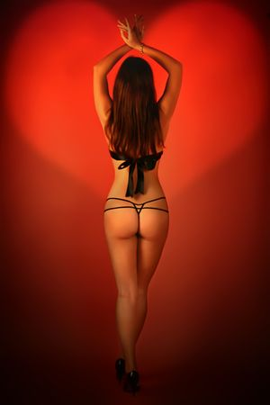 erotic fantasy: beautiful brunette on a red background Stock Photo