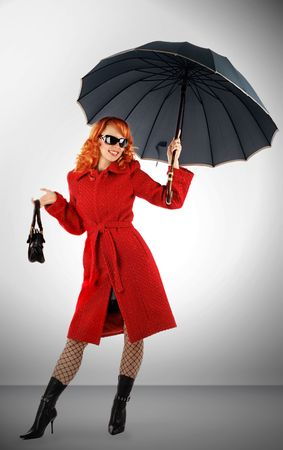 Portrait of the stylish young woman with an umbrella in a red coat Stock Photo - 3828754