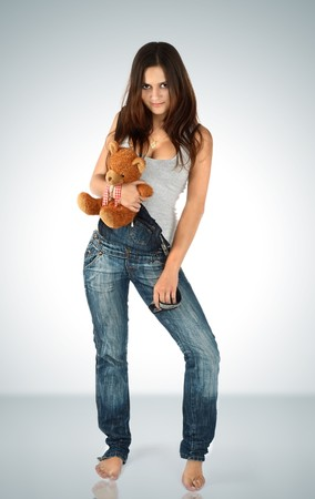 Portrait of the young beautiful brunette with a teddy bear on a white background photo