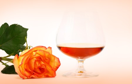 Glass of cognac and rose isolated on a pink background photo