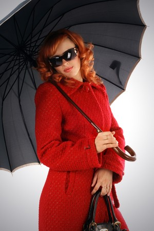 Portrait of the stylish young woman with an umbrella in a red coat photo