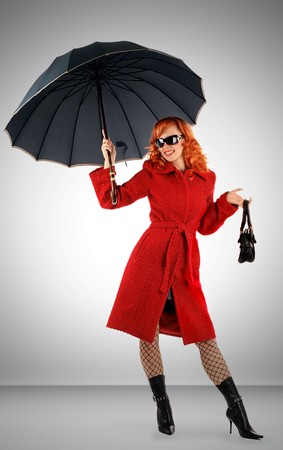 Portrait of the stylish young woman with an umbrella in a red coat Stock Photo - 3940525