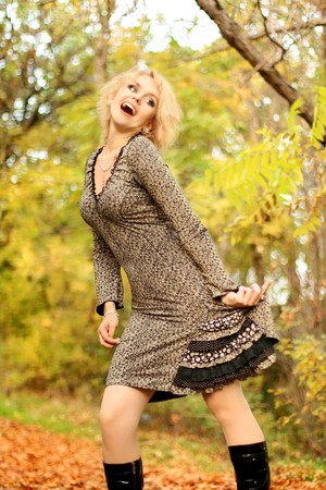 Portrait of the beautiful and happy blonde against red autumn leaves photo