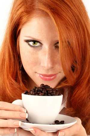 demitasse: young red-haired girl in the dress of the secretary poses with a coffee cup. Pictures well approach for advertising of coffee and cafe
