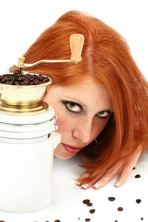 young red-haired girl in the dress of the secretary poses with a coffee grinder. Pictures well approach for advertising of coffee and cafe photo