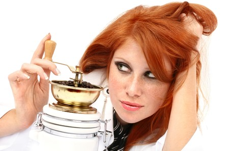 vivacity: young red-haired girl in the dress of the secretary poses with a coffee grinder. Pictures well approach for advertising of coffee and cafe