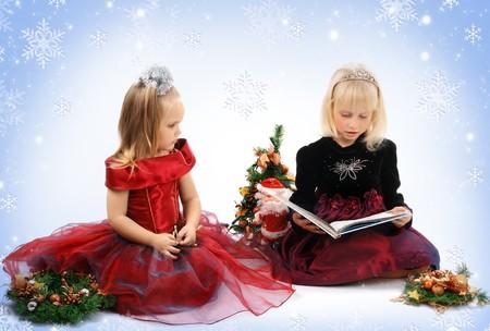 Dos pequeñas niñas en amigos vestidos de princesas celebrar la Navidad Foto de archivo.