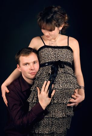 Young beautiful married couple the birth of the second child wait. Dark background. New photos every week photo
