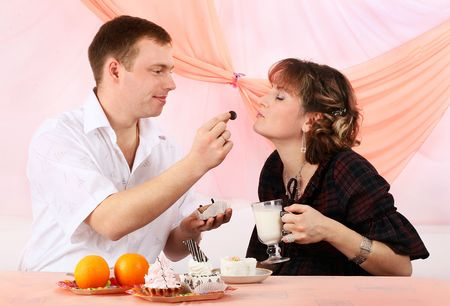 Young couple in love feeding each other with cake photo
