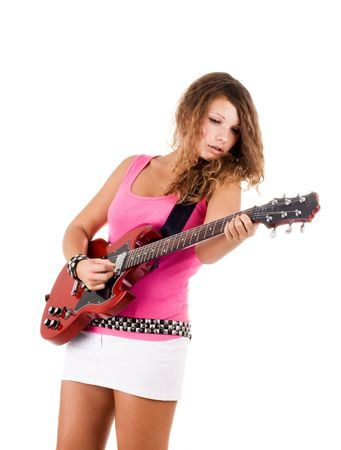 Series. Beautiful brunette with a curly hair poses in studio with a guitar photo
