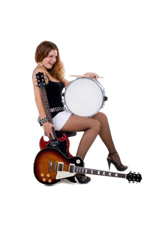 sg: Series. Beautiful brunette with a curly hair poses in studio with a guitars and snare drum