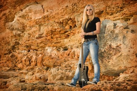 Series. The beautiful blonde with a guitar on rock background photo