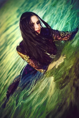 A series. A portrait of the young beautiful brunette in the sea photo
