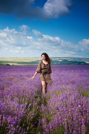 Serie. Chica joven hermosa en el vestido de color marrón en el campo de lavanda