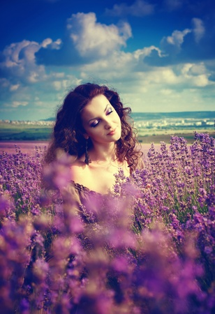 Series. Hermosa joven en el vestido de color marrón en el campo de lavanda