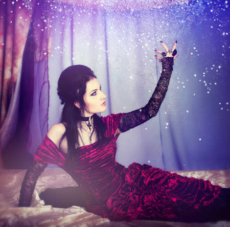 Series. A portrait of the girl in Gothic style on a beautiful bed photo