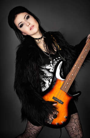 series. Fashion style photo of young rocked woman in studio  with guitar photo