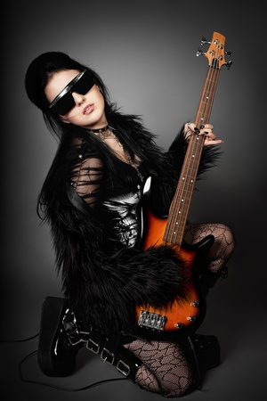 full metal jacket: series. Fashion style photo of young rocked woman in studio  with guitar