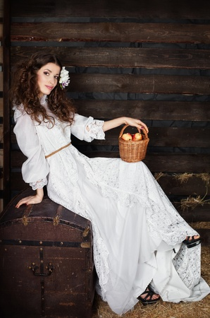 The woman in a long white dress with a wattled basket in hands on a mow Stock Photo - 12703965