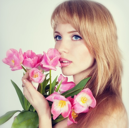 Series. Picture of happy young blonde woman with colorful flowers photo