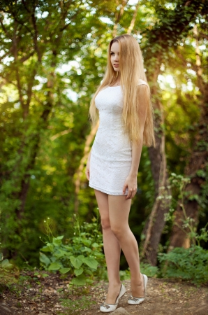 The beautiful blonde in a short white dress walks in the park photo