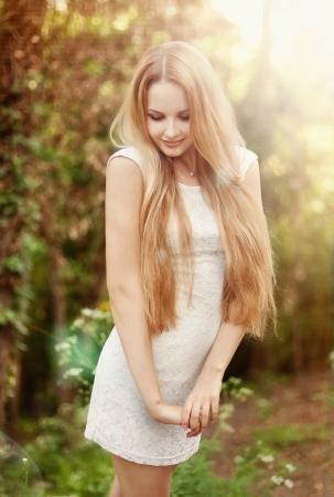 femme blonde: La belle blonde dans une robe courte blanche se promène dans le parc