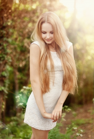 The beautiful blonde in a short white dress walks in the park