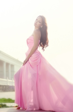 The beautiful harmonous girl in a long pink dress