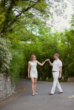 Portrait of young happy smiling cheerful attractive couple together, outdoors photo