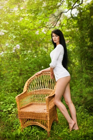 Stunning brunette beauty sitting on a chair photo