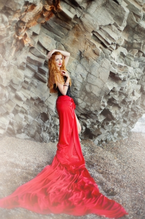The beautiful red-haired girl poses on a sandy beach photo