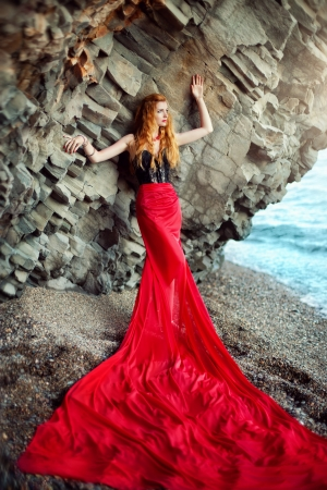 The beautiful red-haired girl poses on a sandy beach Stock Photo - 14530264