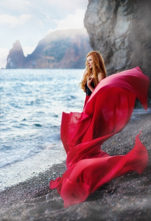 The beautiful red-haired girl poses on a sandy beach Stock Photo - 14530215