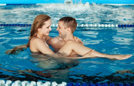 Beautiful happy man and woman couple relaxing by the side of a sun bathed swimming pool Stock Photo
