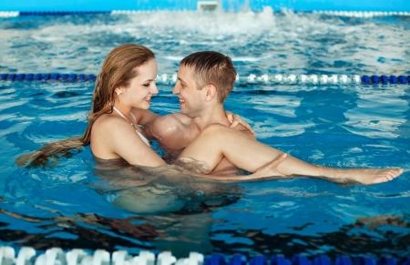 wealthy lifestyle: Bella coppia di uomo felice e donna di relax ai bordi di una piscina soleggiata piscina Archivio Fotografico