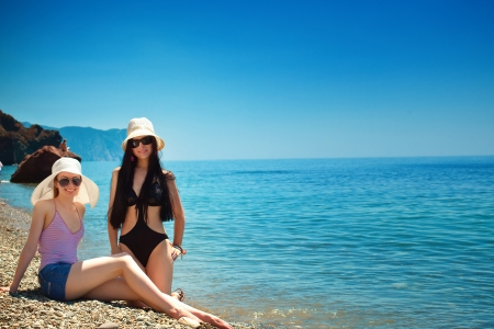 scincare: Young happy beautiful woman lying on sea beach Stock Photo