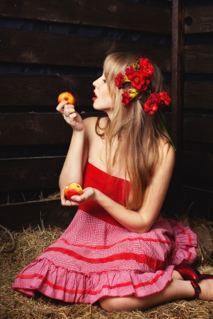 woman in a red dress with an apple in hands on a mow photo