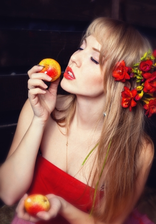 mow: woman in a red dress with an apple in hands on a mow Stock Photo