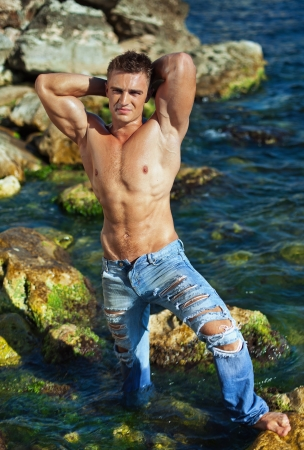 wet jeans: young atractive man staying in the sea