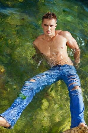 pantalones vaqueros mojados: joven atractiva su estancia en el mar