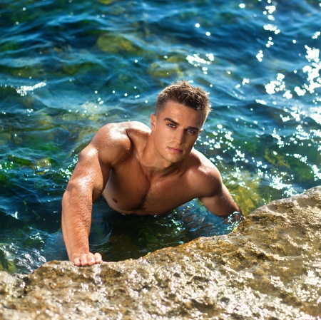 young atractive man staying in the sea